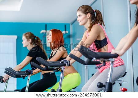 Fitness classes at the gym. Athletic girl pedaling on the simulator until her four girlfriends athletes pedaling on a stationary bike at the gym. - stock photo