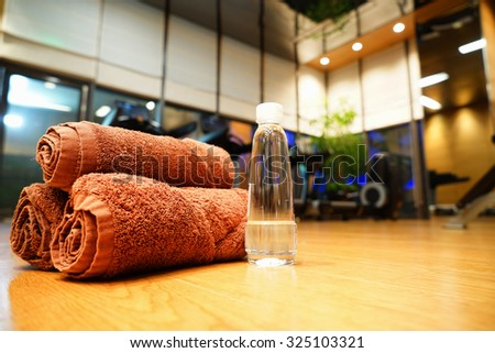 Fitness club concept, towels,water and training equipment. - stock photo