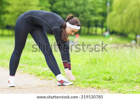 Fitness Concept: Caucasian Woman Stretching Body During Outdoor Workout In the Summer City Park. Horizontal Image