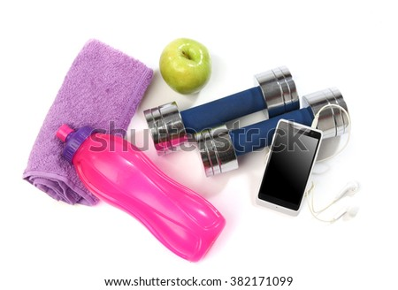 Fitness concept with a bottle of water, a towel, dumbbells, apples and a smartphone isolated - stock photo