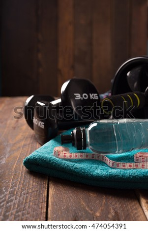 fitness concept with dumbbell,  roller and water
