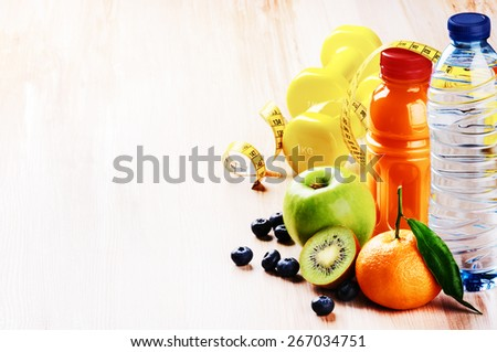 Fitness concept with dumbbells and fresh fruits. Copy space - stock photo