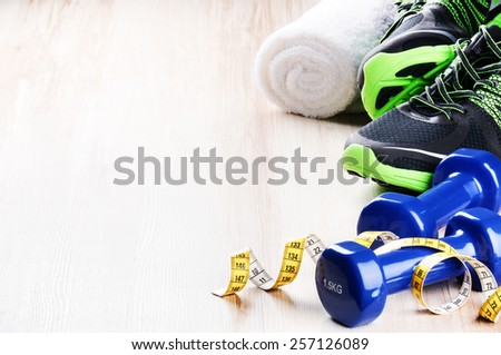 Fitness concept with dumbbells and sneakers - stock photo