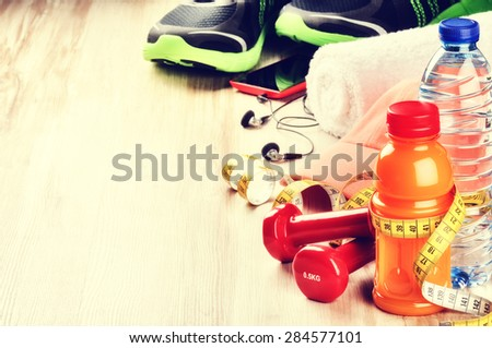 Fitness concept with dumbbells, fruits juice and sportswear. Copy space  - stock photo