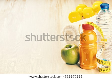 Fitness concept with dumbbells, green apple and water bottle - stock photo