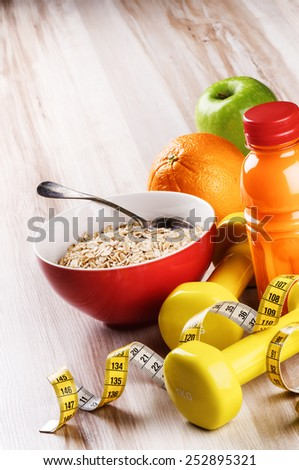 Fitness concept with dumbbells, oatmeal and fresh fruits  - stock photo