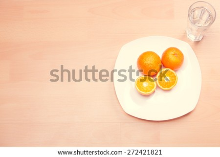 Fitness concept with healthy dieting.Concept of diet.Low-calorie fruit diet.Diet for weight loss.Plate with oranges on the table.Vegetarian diet for weight loss.Healthy snack between meals concept - stock photo