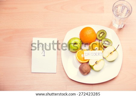 Fitness concept with healthy dieting.Concept of diet.Low-calorie fruit diet.Diet for weight loss.Plate with fruit on the table.Vegetarian diet for weight loss.Healthy dessert for the summer diet - stock photo