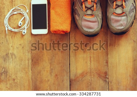 fitness concept with mobile phone with earphones, towel and sport footwear over wooden background - stock photo