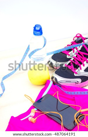 fitness concept with mobile phone with earphones, towel and sport footwear over wooden background