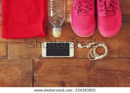 fitness concept with mobile phone with earphones, towel and woman sport footwear over wooden background. - stock photo