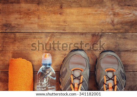 fitness concept with towel and sport footwear over wooden background. top view image  - stock photo