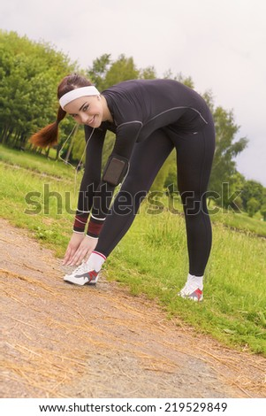 Fitness Concept: Young Attractive Woman Stretching Prior to Regular Jogging Exercise Outdoor Listening to Music. Vertical Image - stock photo