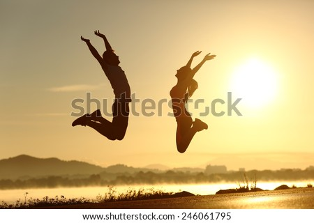 Fitness couple jumping happy at sunset with the sun in the background - stock photo
