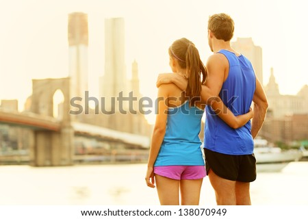 Fitness couple relaxing after running in Brooklyn, New York City, USA. Happy sporty fit young interracial couple enjoying view of Brooklyn Bridge after jogging training outside. Woman and man in 20s. - stock photo