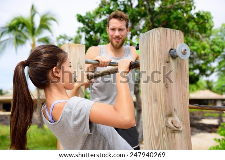 Fitness couple training on chin-up bar together. Woman helped by friend or personal trainer in coaching session supervising exercises on outdoor beach gym. - stock photo