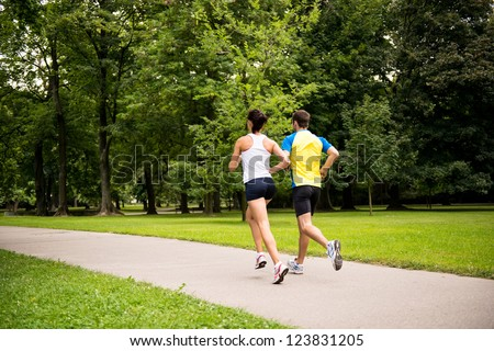 Fitness couple - young man and woman jogging in nature - rear view - stock photo