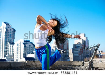 fitness dancing girl on the roof blue sky - stock photo
