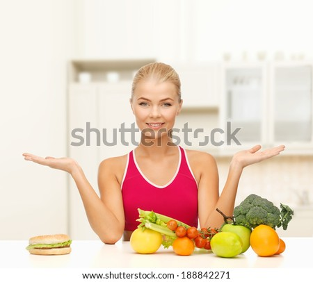 fitness, diet and healthcare concept - smiling woman with fruits versus hamburger