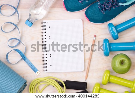 Fitness equipment and blank notebook on wooden background - stock photo