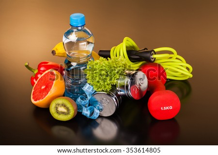 fitness equipment and healthy food on black surface - stock photo