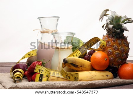 fitness equipment and healthy food - Strawberry Banana smoothie or milkshake(green apple, pepper, grapes, nectarines, kiwi, orange, dumbbells and measuring tape)