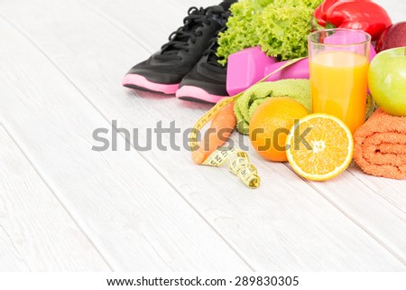 Fitness equipment and healthy nutrition on wood background. - stock photo