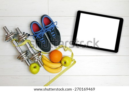 fitness equipment, fruits and blank digital tablet on white wooden floor - stock photo