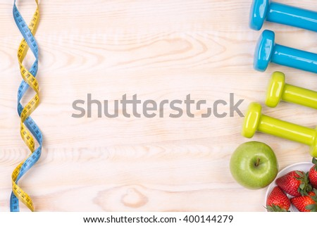 Fitness equipment  on wooden background with copy space - stock photo