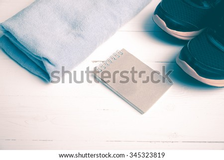 fitness equipment : running shoes,blue towel and notepad on white wood table vintage style