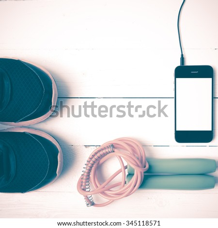 fitness equipment : running shoes,jumping rope and phone on white wood table vintage style