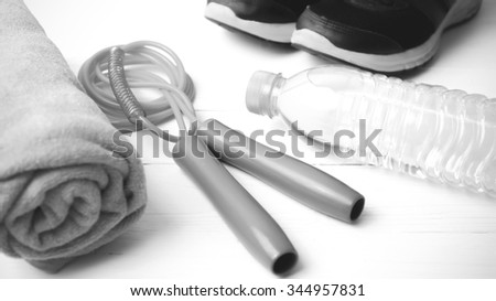 fitness equipment : running shoes,towel,jumping rope and drinking water on white wood table black and white color tone style
