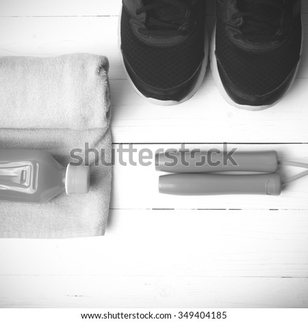 fitness equipment : running shoes,towel,jumping rope and orange juice on white wood background black and white tone color style
