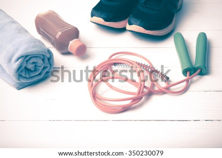 fitness equipment : running shoes,towel,jumping rope and orange juice on white wood background vintage tone style
