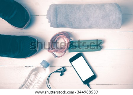 fitness equipment : running shoes,towel,jumping rope,water bottle and phone on white wood table vintage style
