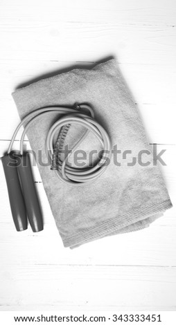fitness equipment:towel,jumping rope on white wood table black and white color style