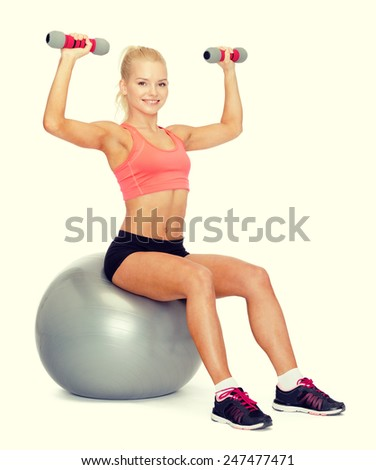 fitness, exercise and diet concept - smiling sporty woman with dumbbells sitting on fitness ball