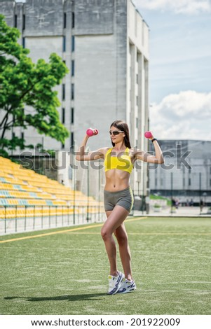 Fitness exercise with dumbbells. Fitness woman in tracksuit and dumbbell training on the football field on a hot sunny day. - stock photo