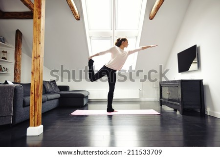 Fitness female exercising in living room. Stretching and balancing on one leg at home. Caucasian female practicing yoga. - stock photo