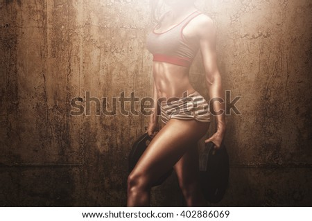 Fitness female model holding weight plates in front of concrete wall preparing for hard training