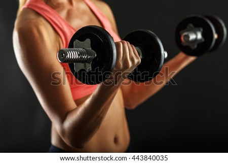 Fitness female woman with muscular body, doing her workout with dumbbells - stock photo