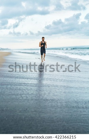 Fitness. Fit Athletic Man Running On Beach. Jogger Exercising And Training For Marathon. Sporty Runner Jogging Near Sea During Outdoor Workout. Sports, Healthy Active Lifestyle Concept - stock photo