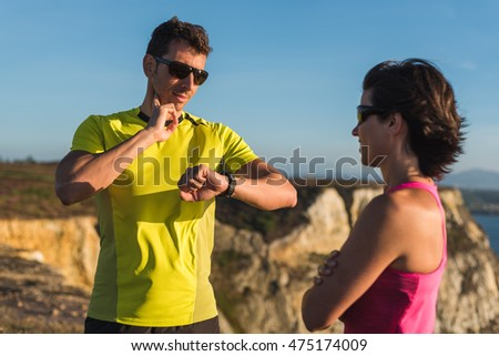 Fitness fit runner man smiling checking heart rate with watch and trainer during outdoor trail running workout. Couple doing sport outside together training for a marathon or decathlon competition.