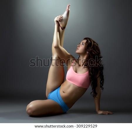 Fitness. Flexible brunette training in studio - stock photo