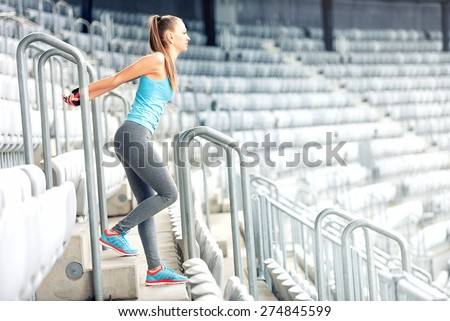 Fitness girl doing fitness exercises and working out on stadium stairs. Jogger on morning training, healthy lifestyle routine concept - stock photo