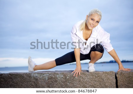 Fitness girl doing stretching exercise at the beach. - stock photo