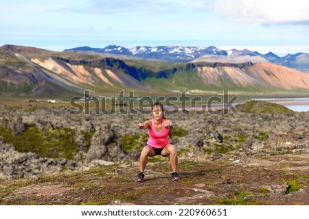 Fitness girl exercising outdoors doing jump squat in amazing nature landscape. Fit female woman athlete cross-training outside. Image from Iceland. - stock photo