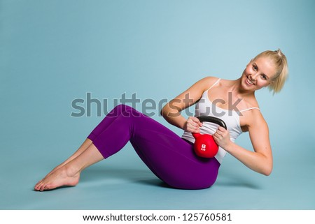 Fitness girl in Russian twist position with a kettlebell - stock photo