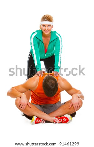 Fitness girl in sportswear helping guy doing stretching exercise on floor - stock photo