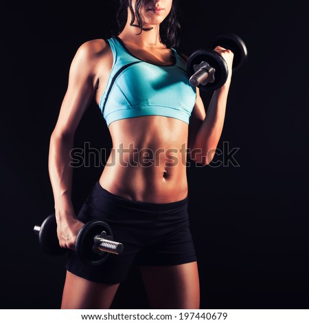 Fitness girl in training with dumbbells